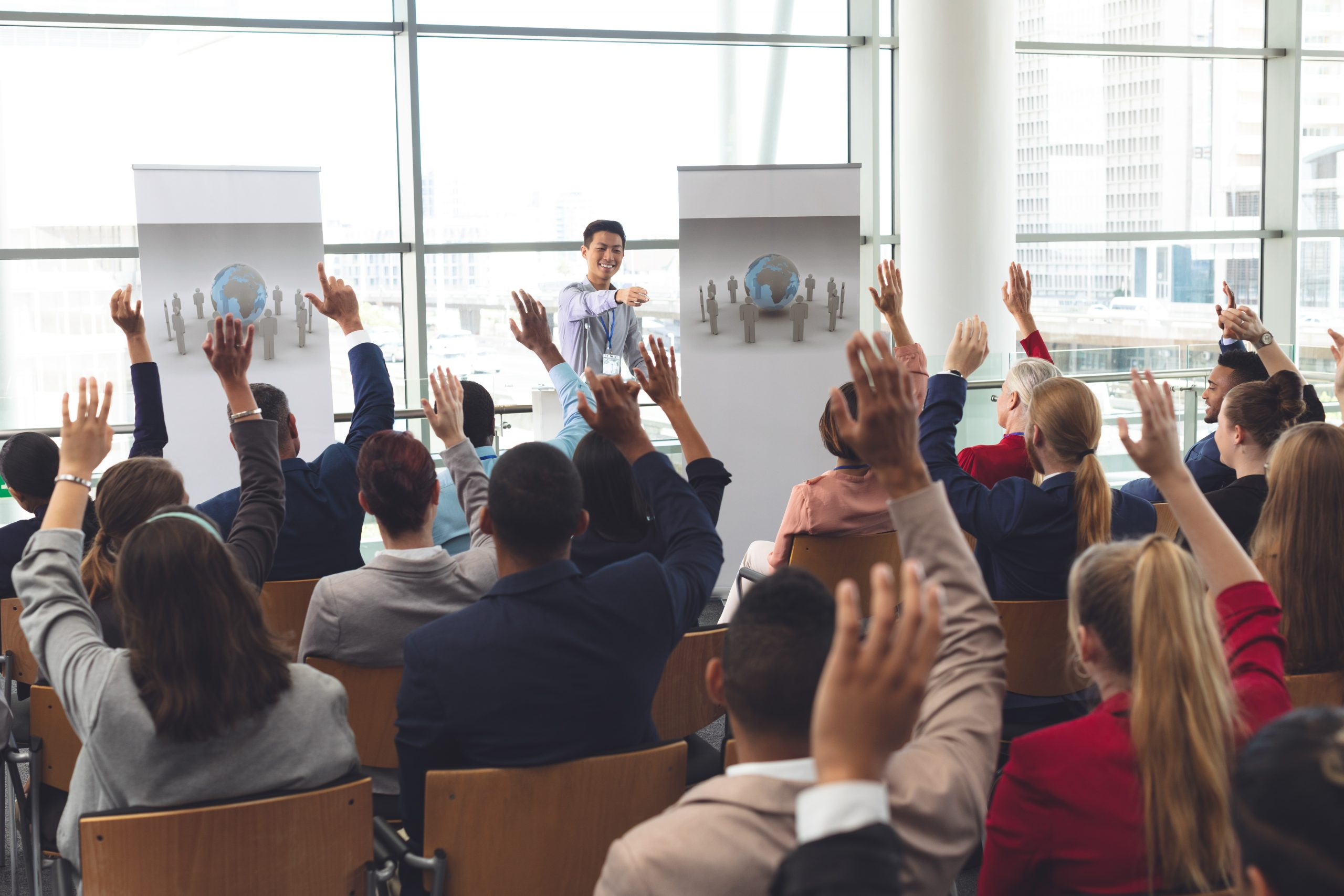 Business people raising hands in a business seminar